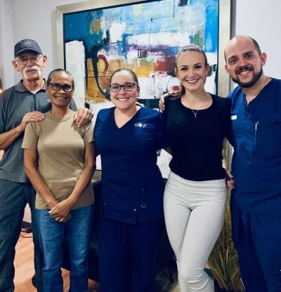 Dr. Josúe Chavés, Oral Surgeon and Vayolla Quíros, Office Manager with happy patients