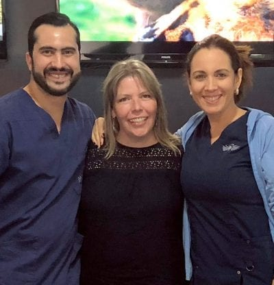 Dr. Andres Brenes, prothodontist and Dr. Karen Yurell, Patient Coordinator with a happy patient